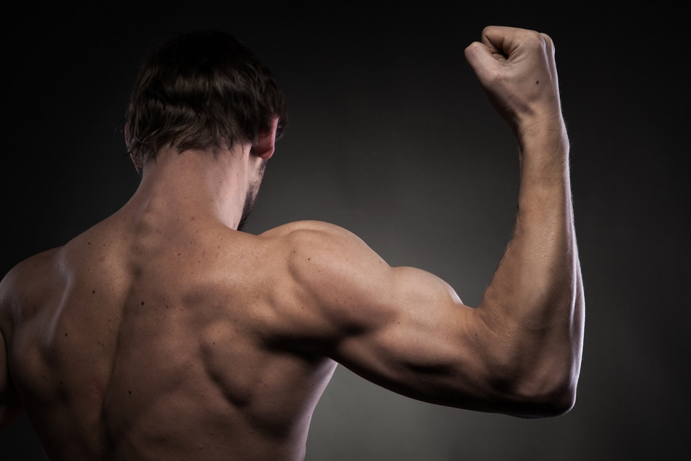 healthy-man-flexing-arms-from-behind (133557608)